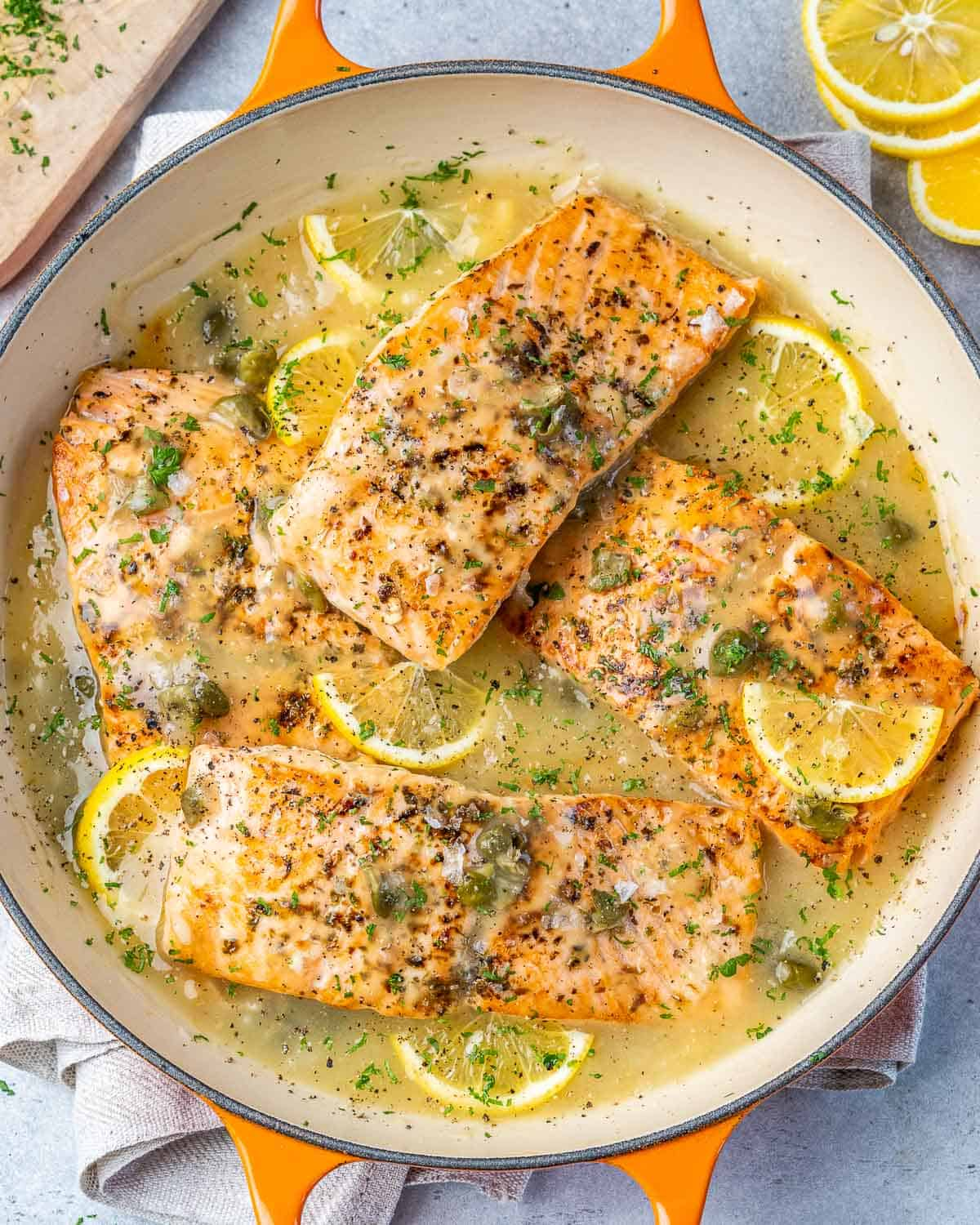 top view salmon piccata on an orange dish