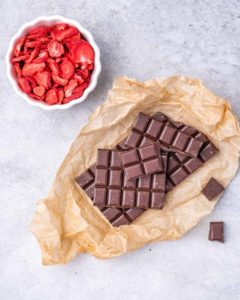 2 ingredients on a board, dark chocolate and dried strawberries