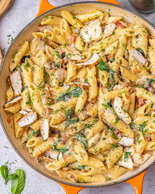 chicken and spinach pasta in an orange dish
