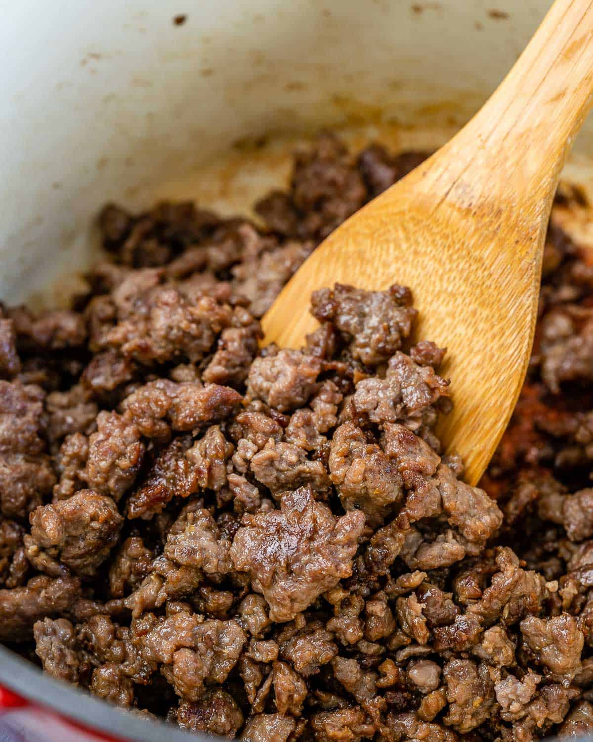 Ground beef browned in pot with wooden spoon.