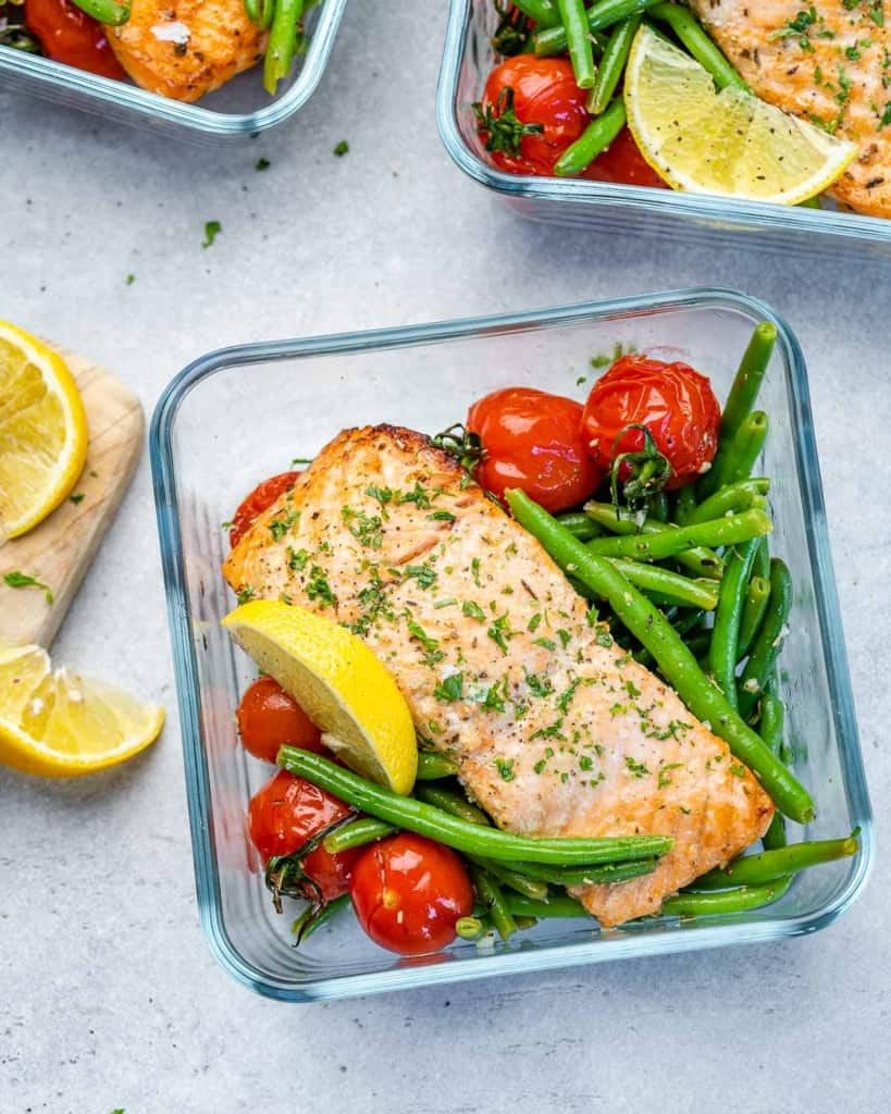 One meal prep bowl filled with salmon, tomatoes, and green beans