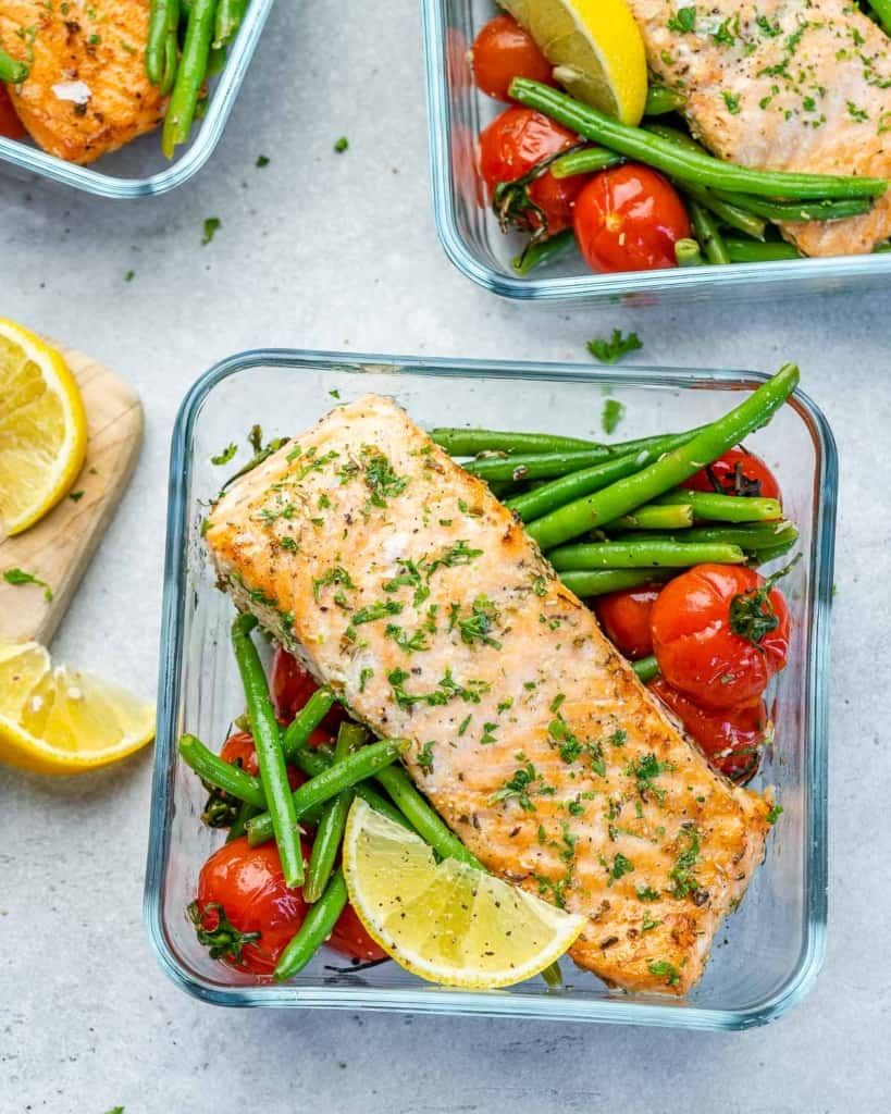 Top view of three salmon meal prep bowls with green beans and tomatoes