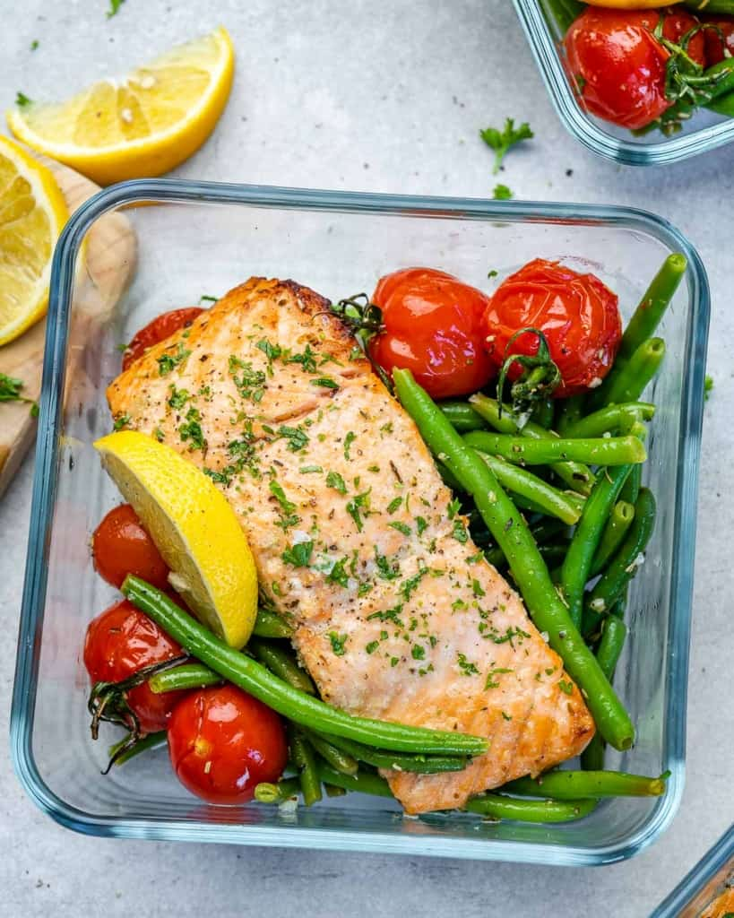 Salmon sitting on top of tomatoes and green beans
