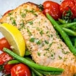 One salmon fillet with green beans, lemon wedge, and tomatoes