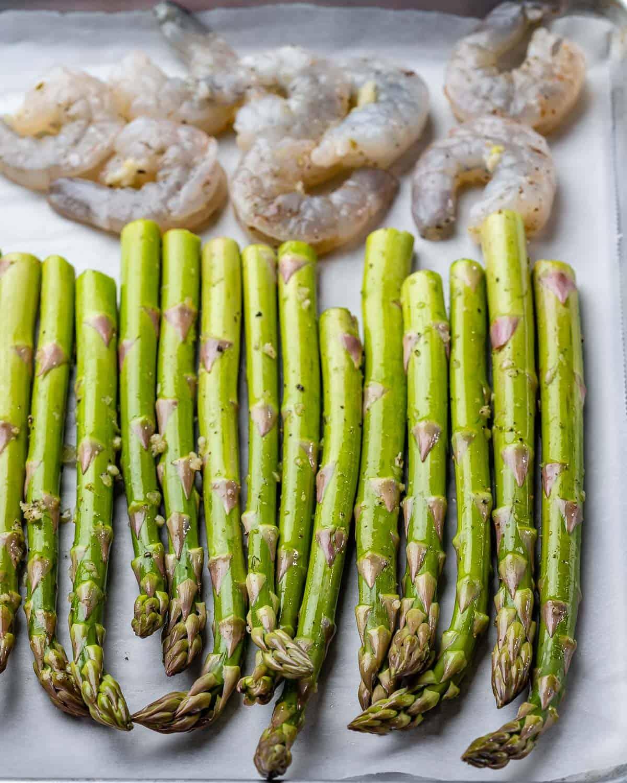 Raw asparagus and shrimp ready to bake on sheet pan.