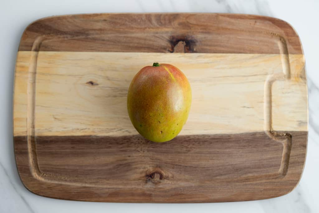 top view of one mango in a cutting board