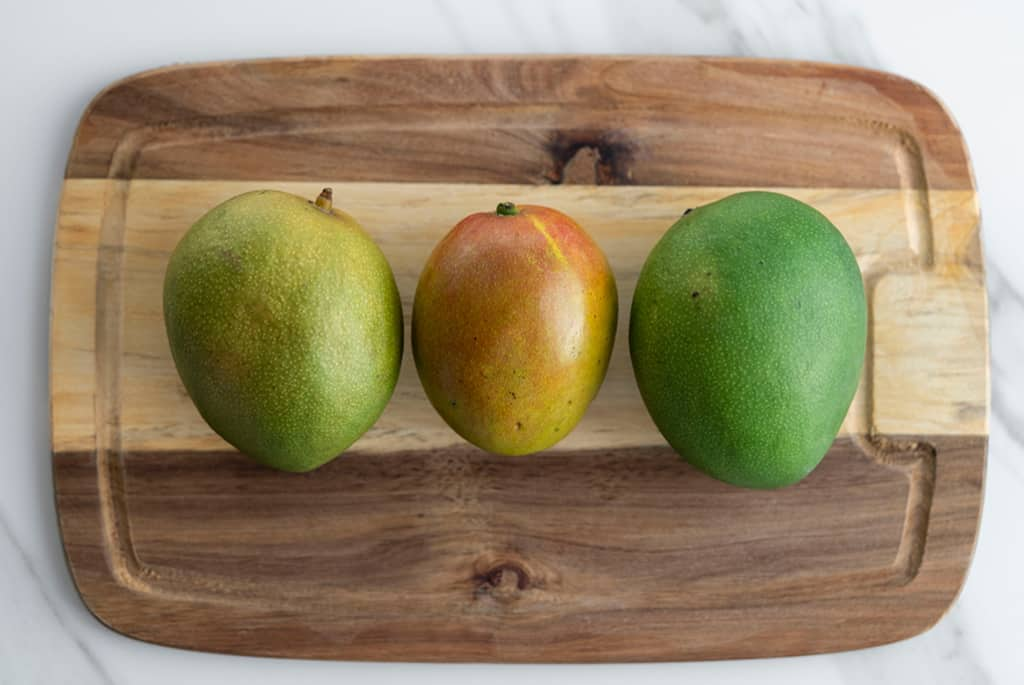 top view of 3 mangos on a cutting board