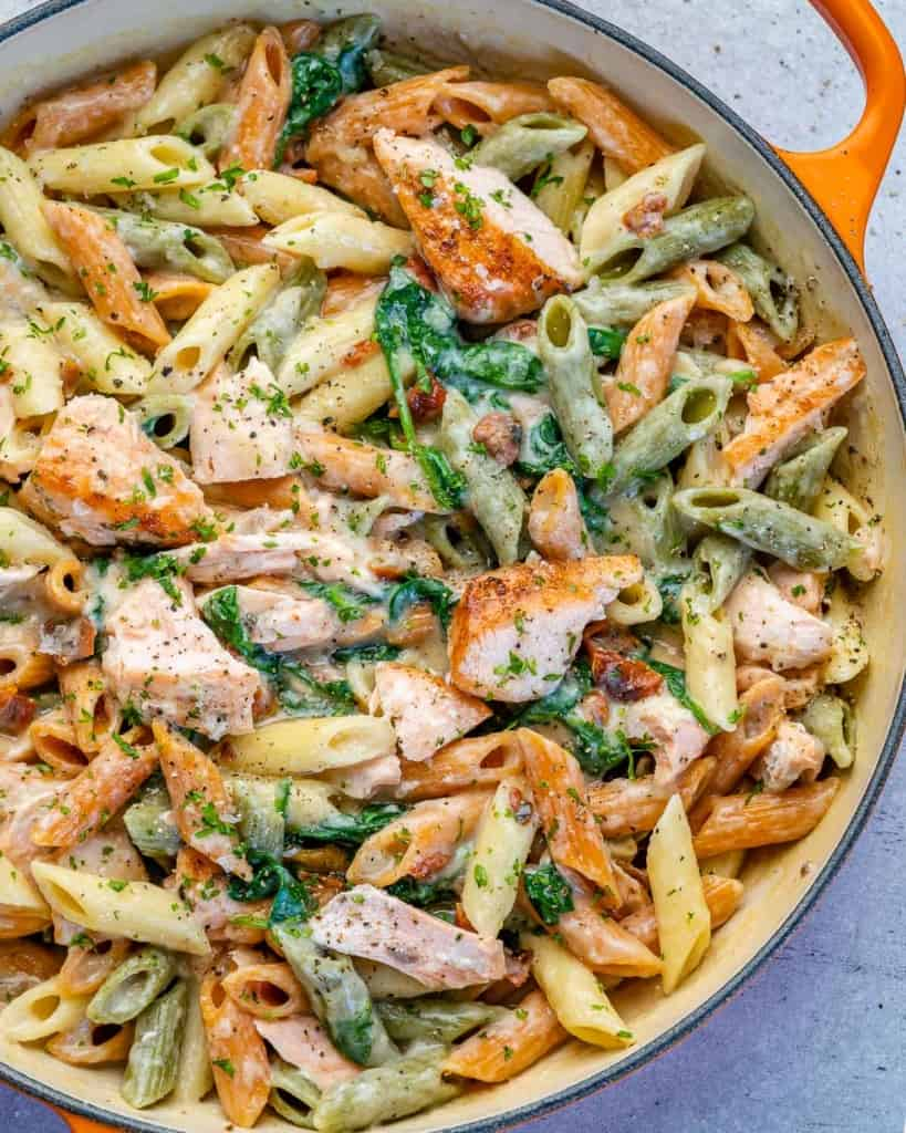 top view salmon and pasta in an orange skillet