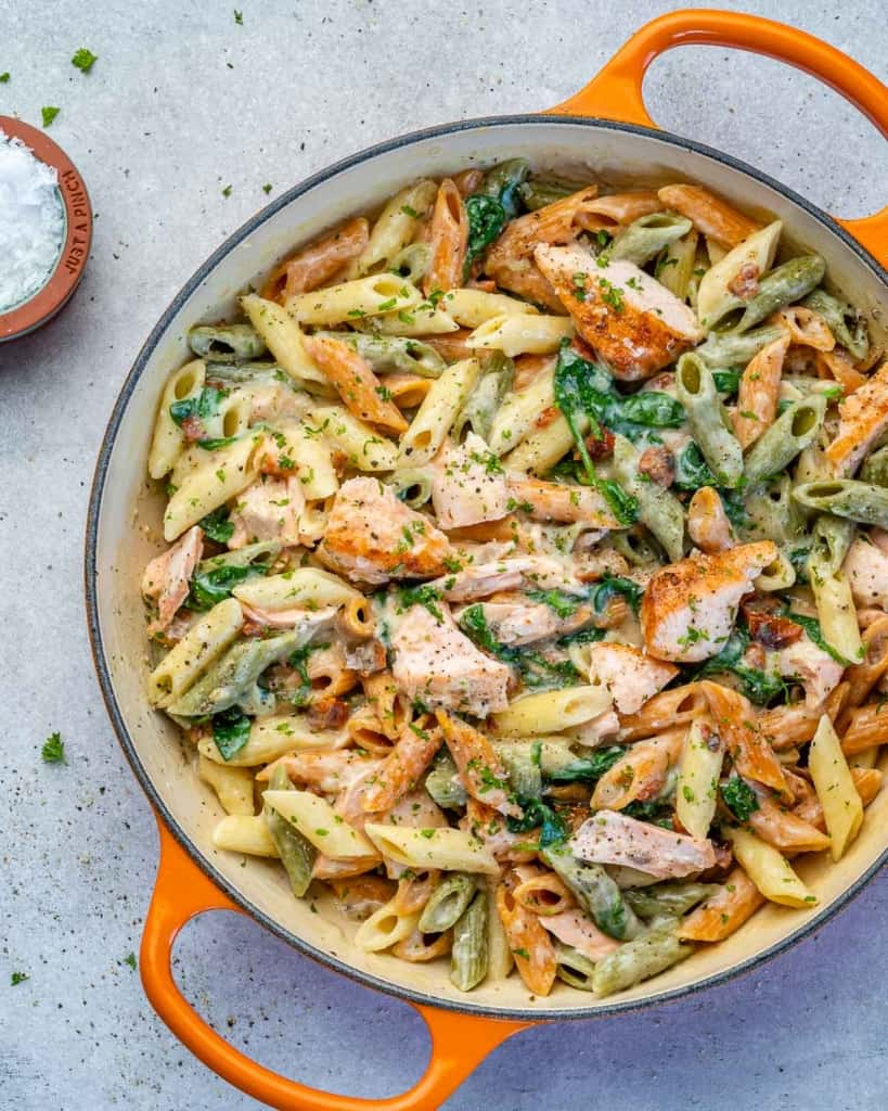 top view of orange skillet with salmon pasta