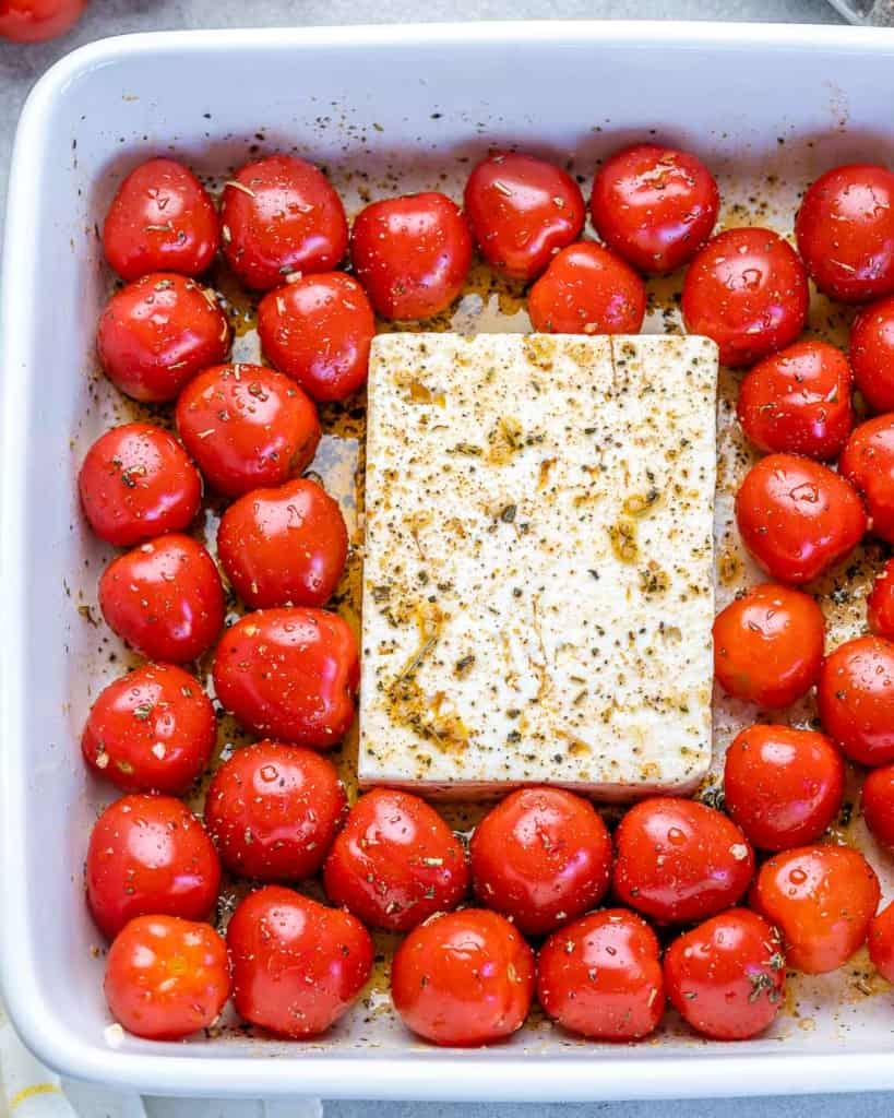 tomatoes and feta in a dish before baking
