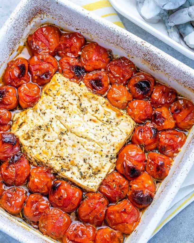 baked tomatoes and block of feta in a white dish