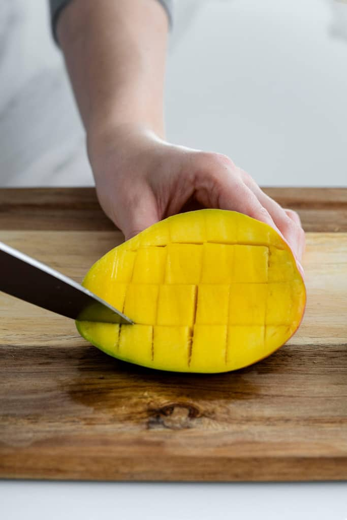knife slicing cubes in mango flesh