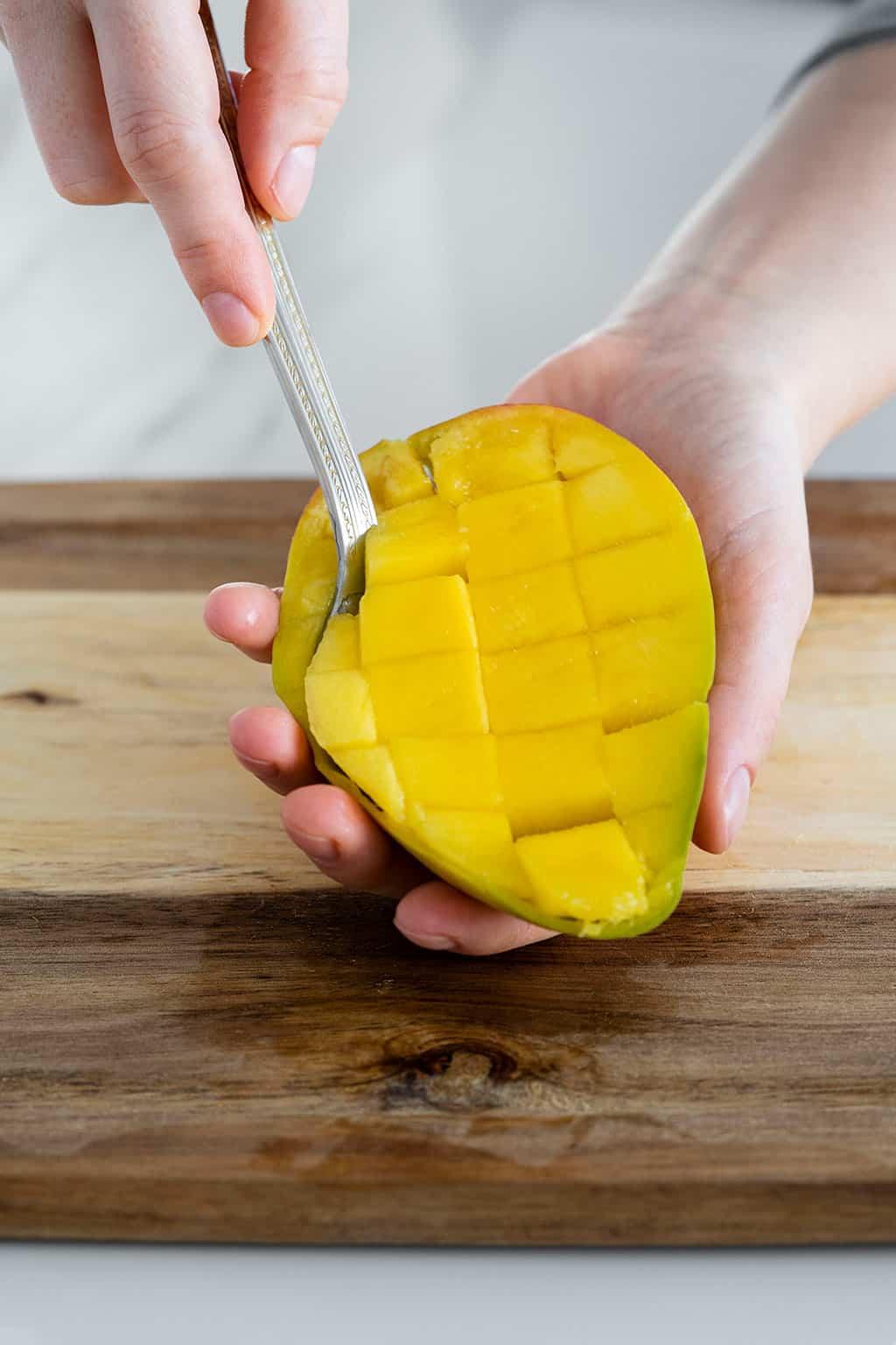spoon scooping mango flesh from mango