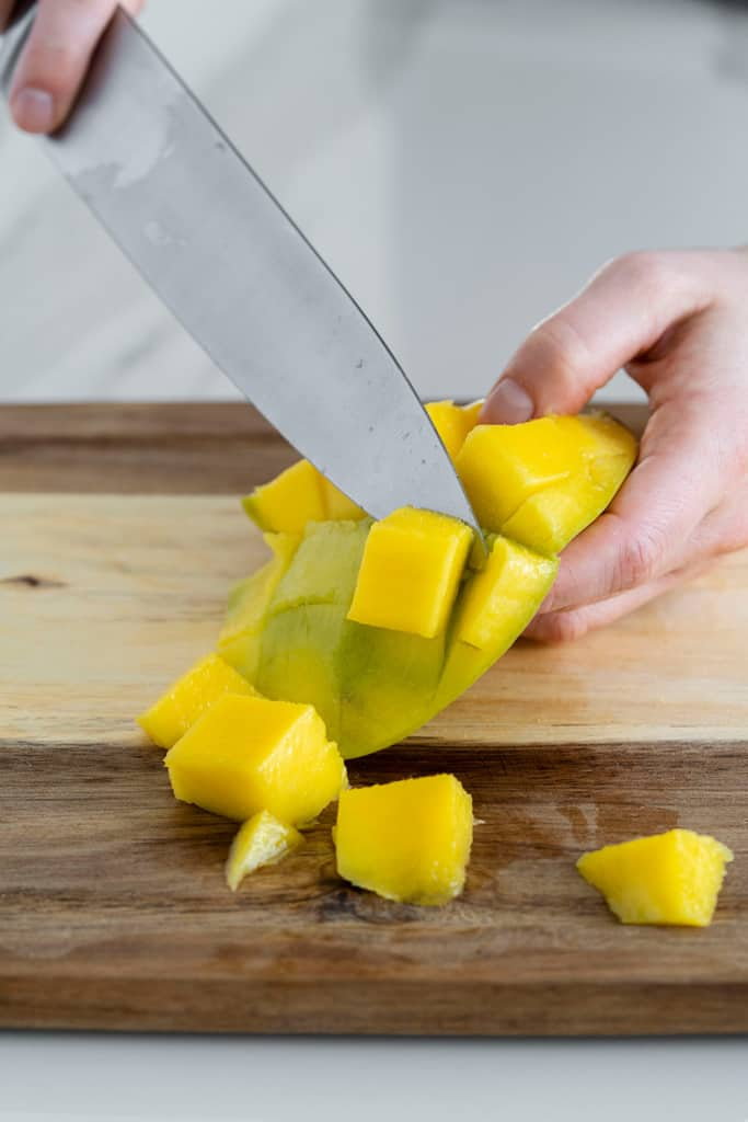 knife slicing off mango piece off skin