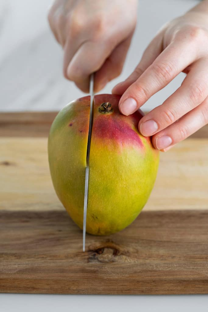 mango stem side up with knife slicing flesh side down