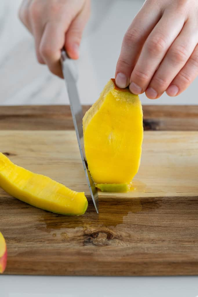side shot of mango flesh being cut from mango