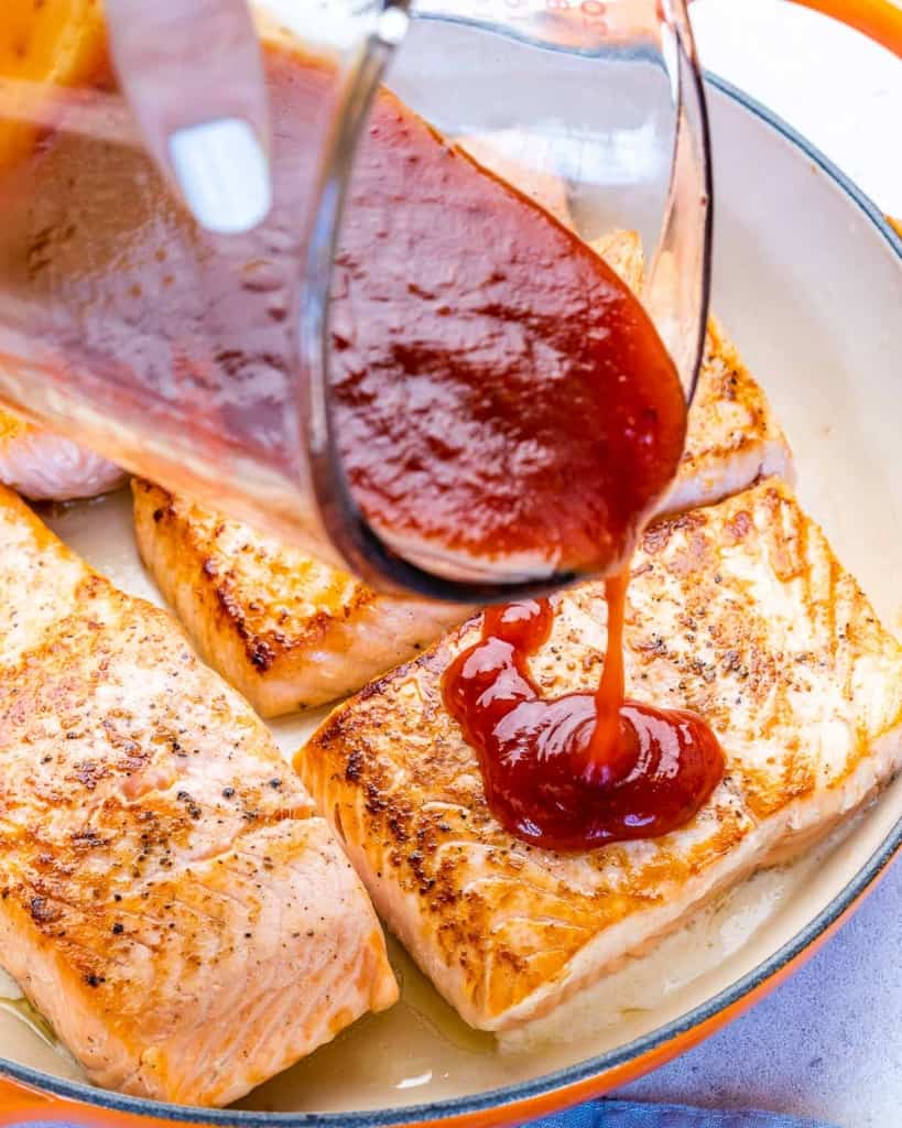 bbq sauce being poured over salmon filets