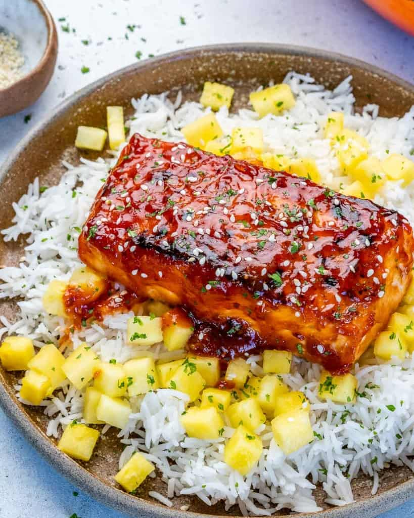 side shot of salmon filet over pineapple and rice