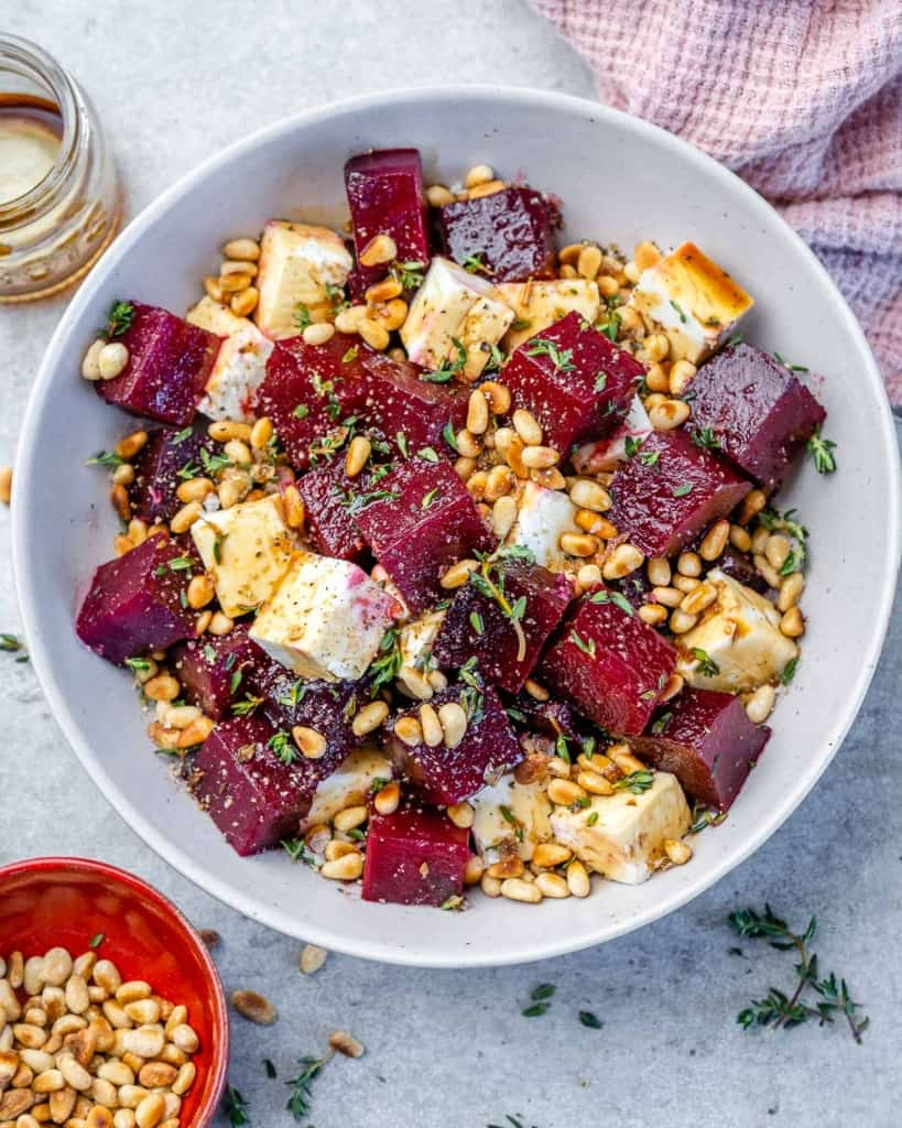 Roasted beet salad in white bowl with pine nuts and pink linen
