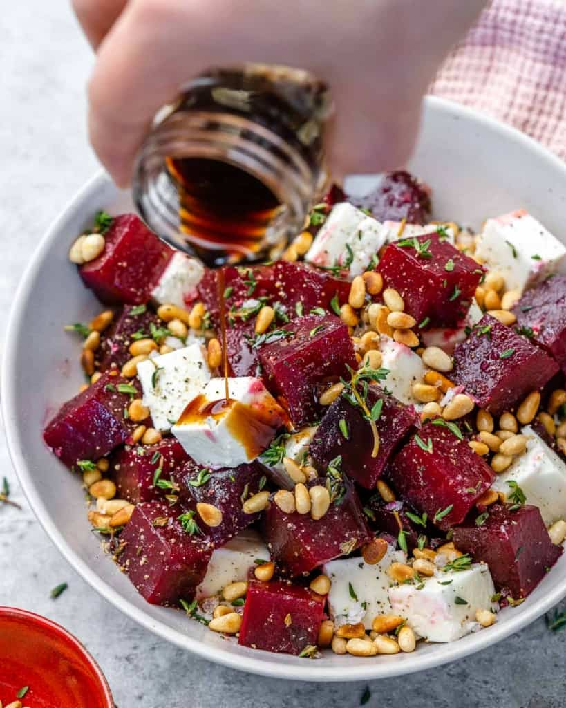 Balsamic vinegar being poured over roasted beet salad in white bowl