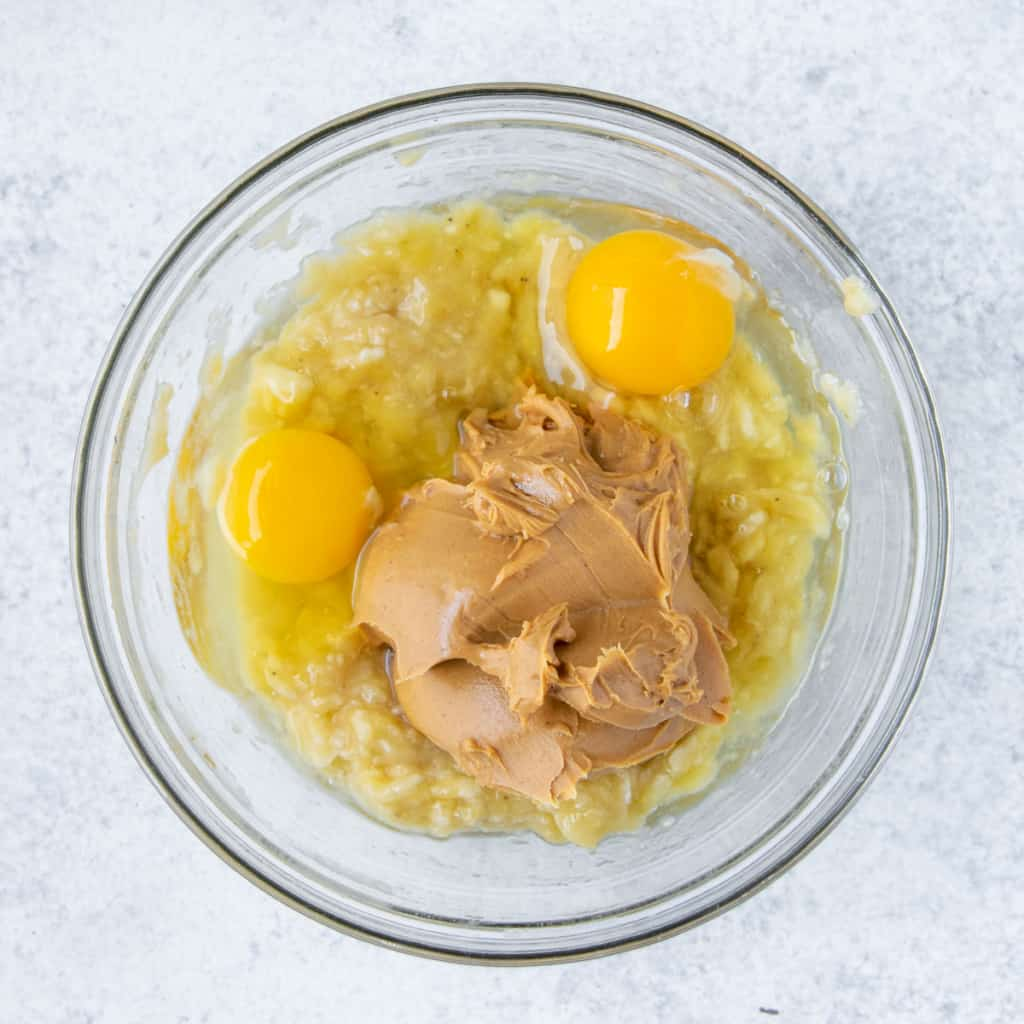 mashed banana, eggs, peanut butter in a bowl