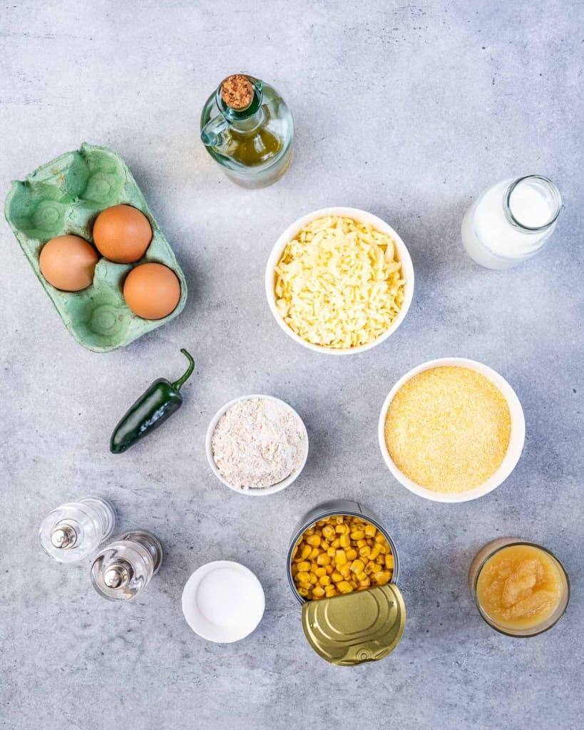 Eggs, shredded cheese, flour, cornmeal, canned corn, butter milk, olive oil, salt, jalapeño, baking powder in bowls