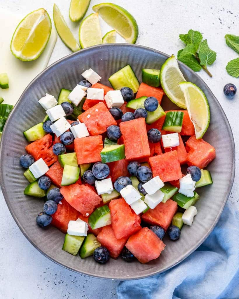 Top view of watermelon feta salad in grey bowl with lime wedges and fresh herbs