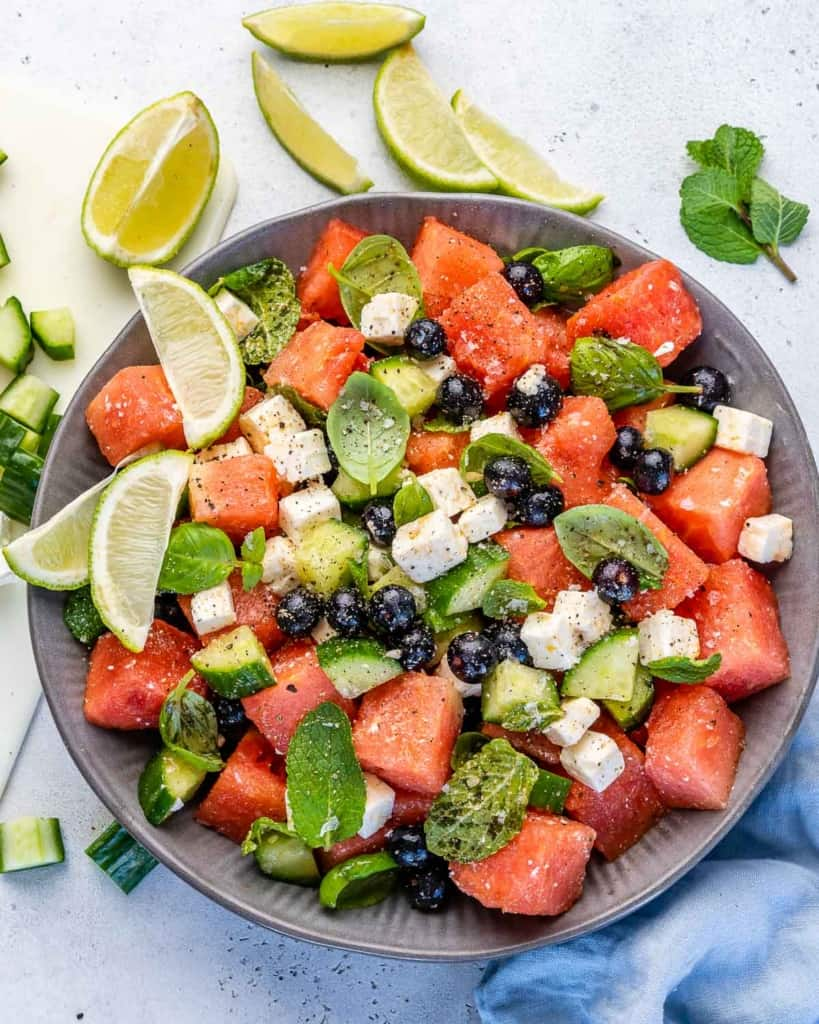 Top view of watermelon feta salad in bowl with lime wedges