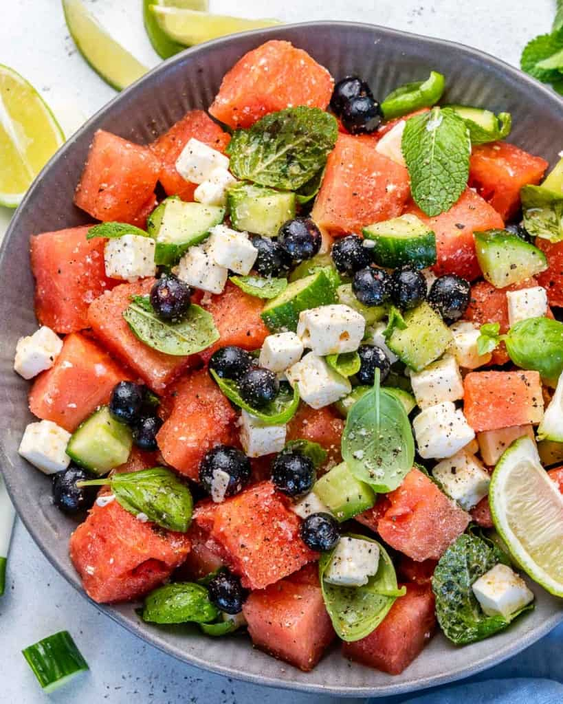 Top view of salad in bowl with lime wedges