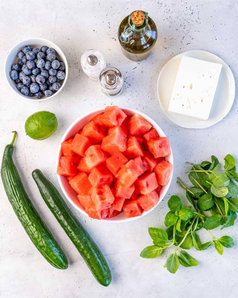 Cucumbers, blueberries, lime, salt, pepper, olive oil, feta cheese, mint, watermelon, and basil for watermelon feta salad