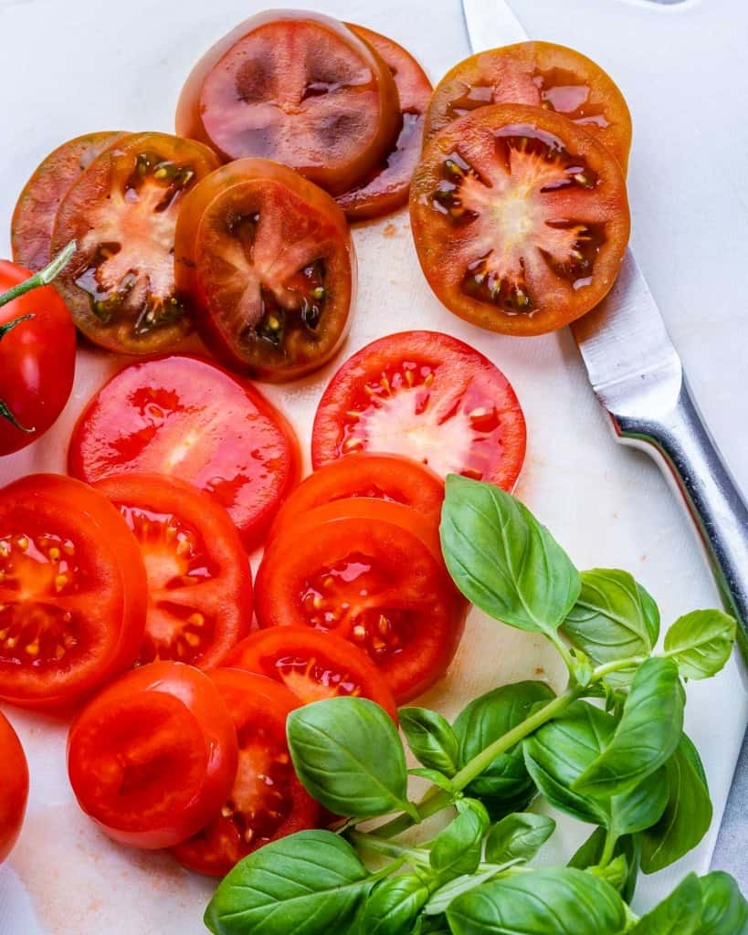 Sliced tomatoes next to basil for caprese salad