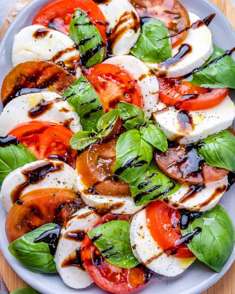 Caprese salad on plate with balsamic drizzle and basil leaves