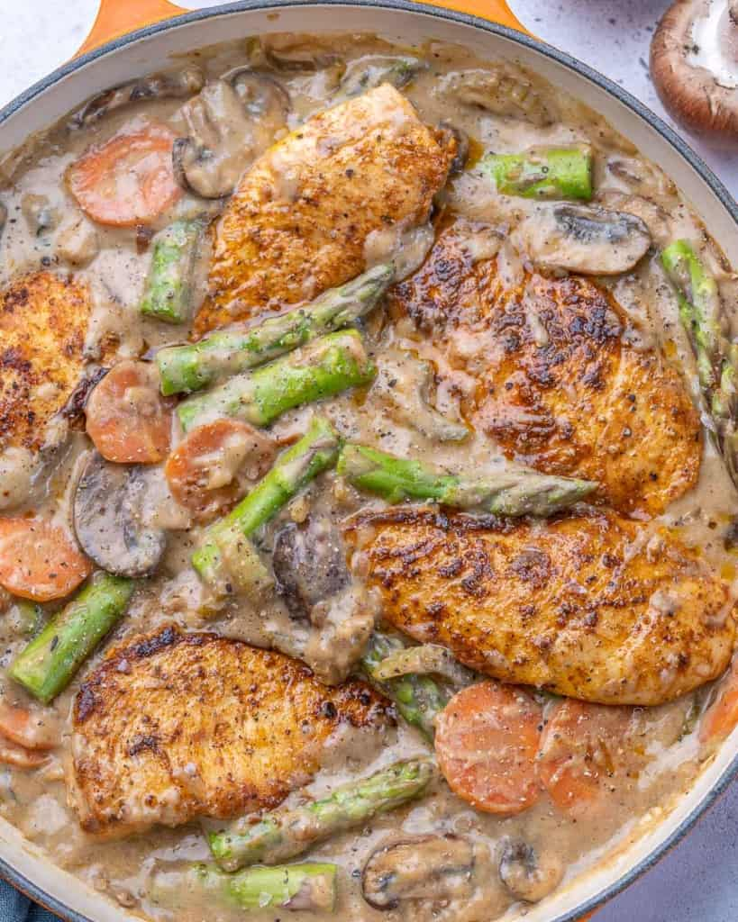 Chicken, asparagus, mushrooms, carrots, and celery in orange pan