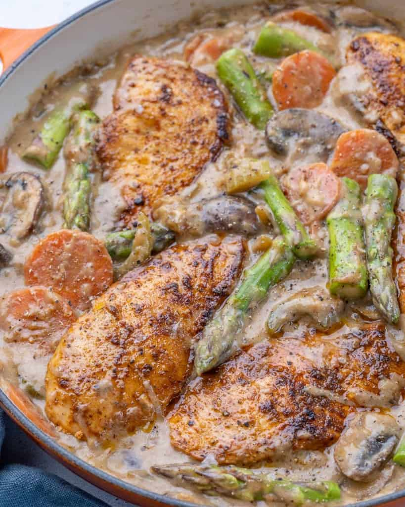 Side view of chicken in pan with asparagus, carrots, mushrooms, and celery