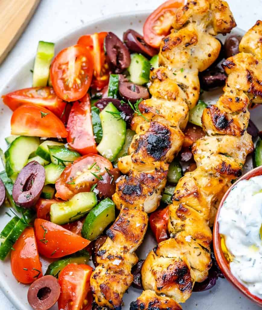close view of chicken souvlaki in bowl with tomatoes and cucumbers with olives