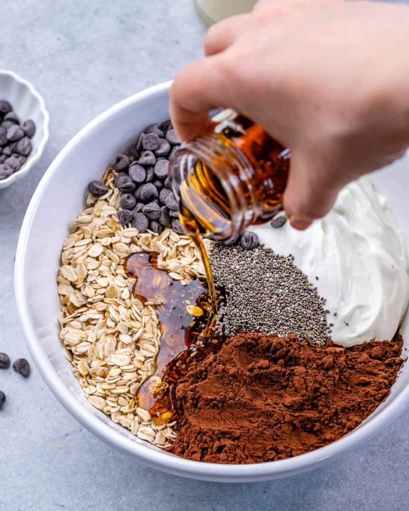 oats, chocolate chips, cacao powder, chia seeds, yogurt, and maple syrup being poured in white bowl