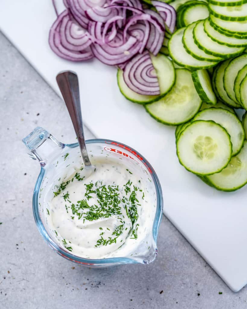 creamy salad dressing in jar next to sliced cucumbers