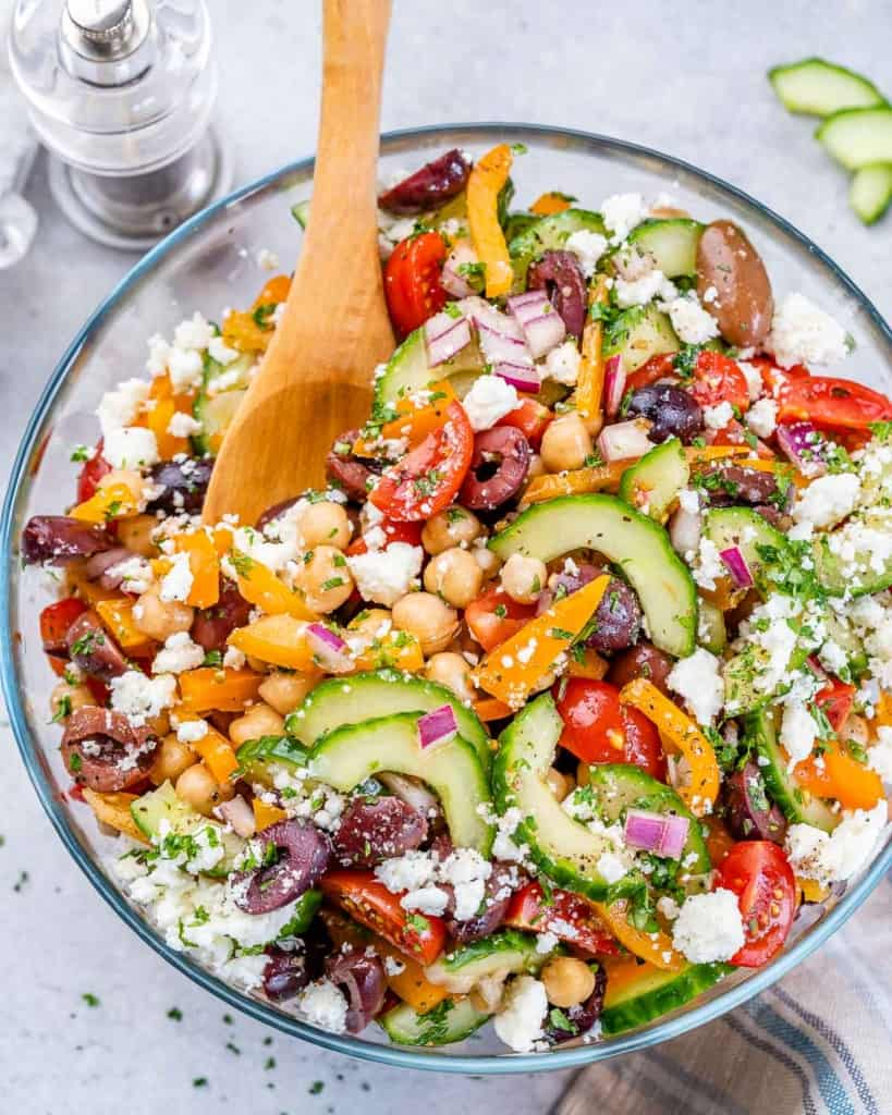 top view chickpea salad in a bowl with wooden spoon in it