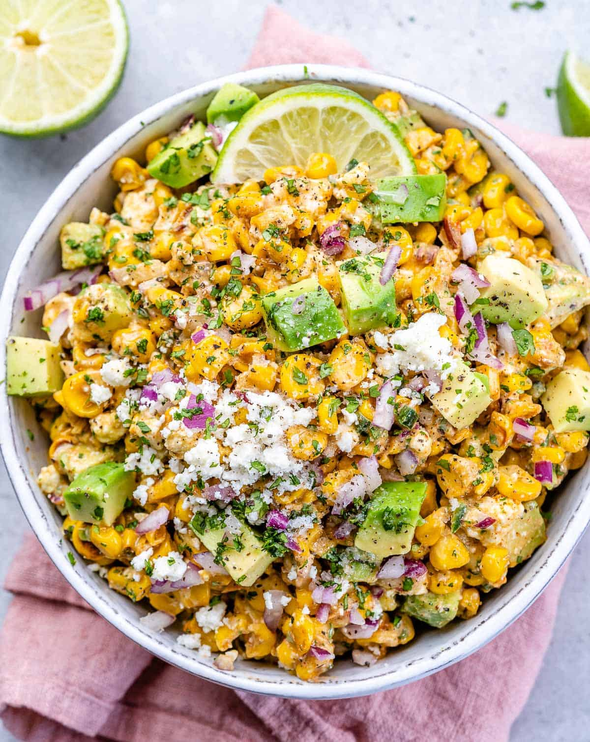 top view street corn salad in a white bowl under a pink napkin