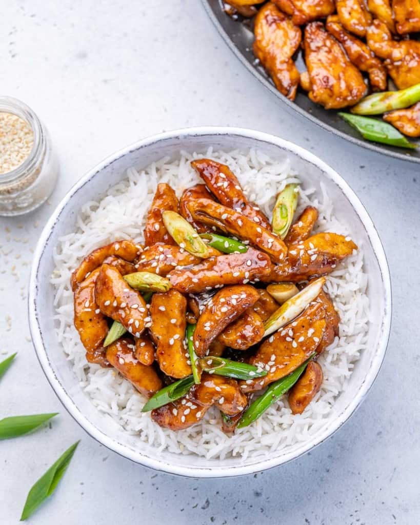 chinese chicken in a bed of rice in a white bowl