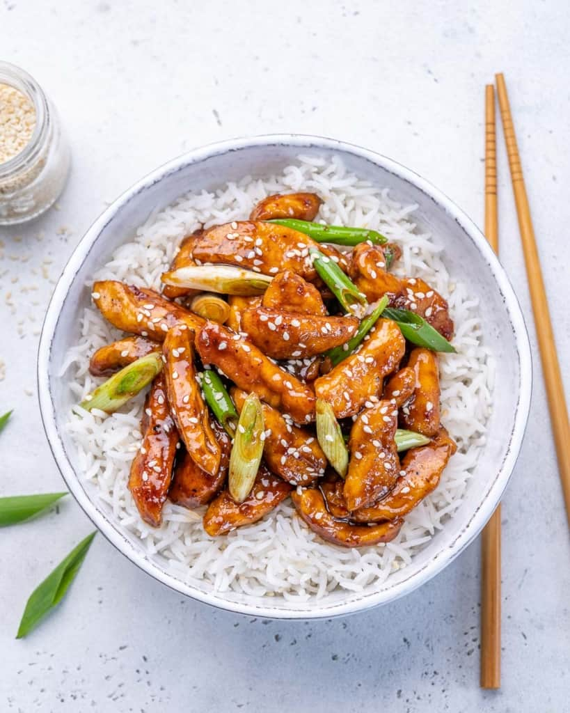 top view asian chicken over a bed of rice in a bowl