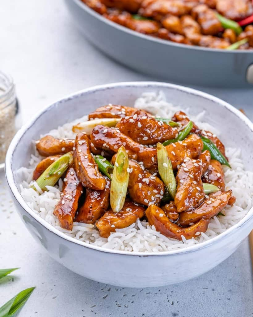 side shot asian chicken with rice in a white bowl