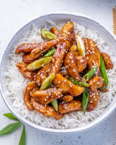 close up top view of mongolian chicken serve over a bowl of rice