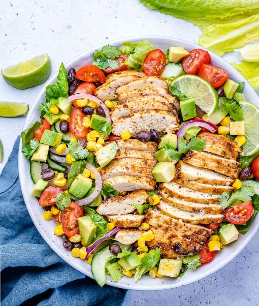 top view of slice grilled chicken over a bed of greens salad in a white bowl