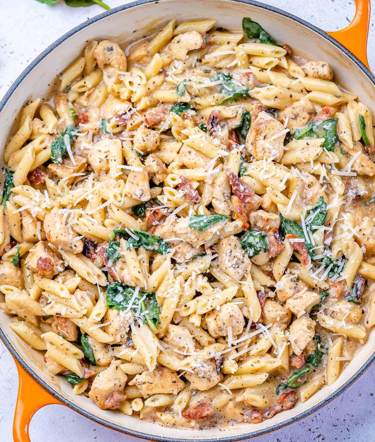 top view chicken pasta with spinach in an orange skillet