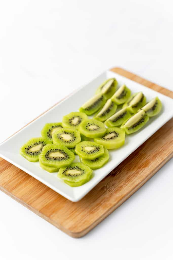 Angled view of cut kiwi on a serving plate.