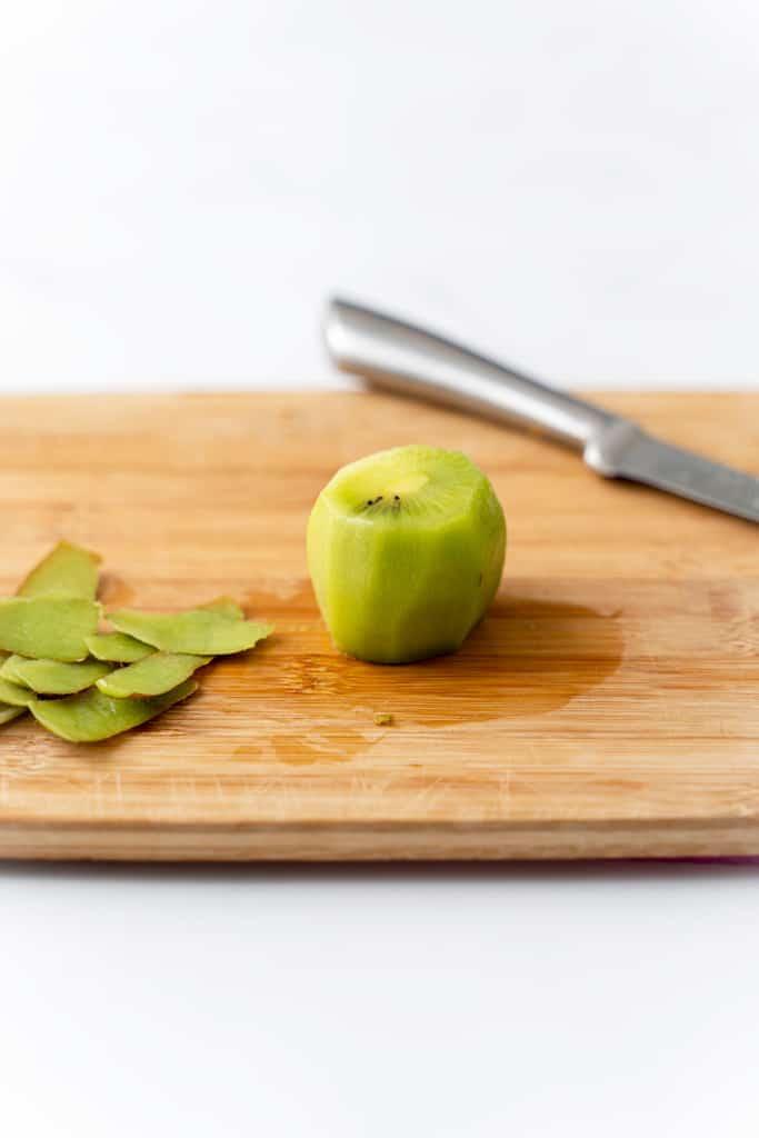 A peeled kiwi on a cutting board.