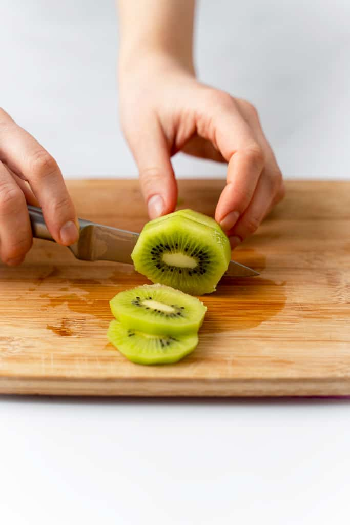 A kiwi being cut into round slices.