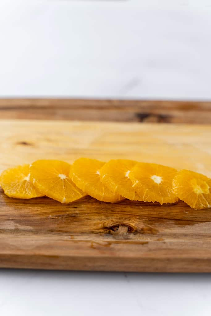 Multiple slices of orange, laid on a cutting board.
