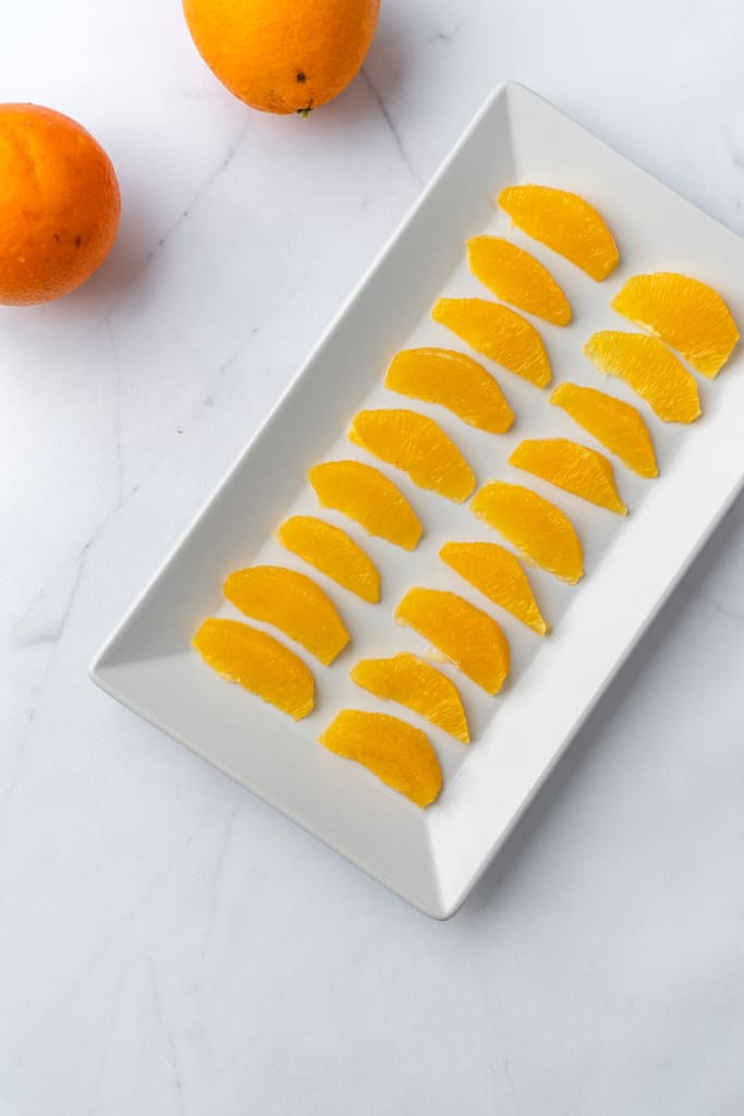 A platter of orange segments laid out.